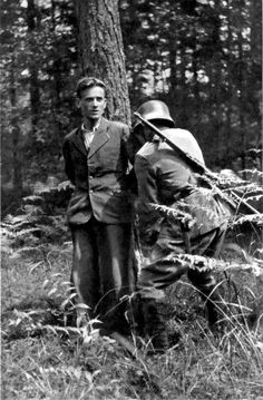 bag-of-dirt:  A German soldier ties the hands of a captured Slovenian partisan prior to his execution on Mala Poljana mountain in the Kamnik-Savinja Alps. Near Lom pod Storžičem, Tržič, Slovenia, Yugoslavia. Summer 1942.