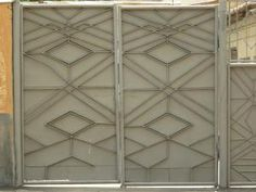 Old grey metal gates with peeling paint and diamond pattern on front.