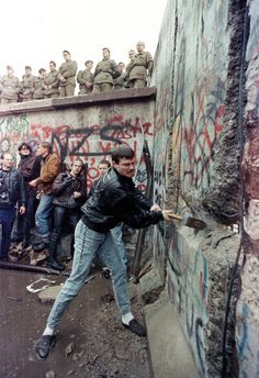 A demonstrator pounds away at the Berlin Wall as East Berlin border guards look on from above the Brandenburg Gate in Berlin in November, 1989.