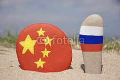 China and Russia's flags on colourful stones with sand background
