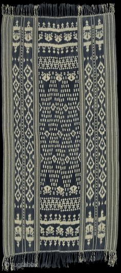 West Sumba, Indonesia, 1950-1960, warp ikat, cotton. Man's wrap, hanggi ngoko, also called hanggi wolo remba. Field covered in characteristic python skin pattern, called rembe, and mamuli, earrings. The use of mamuli ...