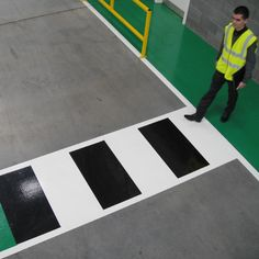 Pedestrian walkway with zebra crossing and a safety barrier.