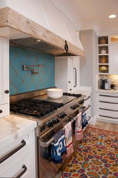 the hood built in, tiles, stove, counters...mediterranean kitchen by Intimate Living Interiors