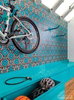As bicicletas forma um painel na sala. E um móvel guarda os acessórios da bike
