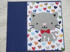 This is a 6x6 inch chipboard album that any cat lover would enjoy. The binding is navy blue and the patterned papers used in the album include bright colors of yellow, blue, red, and green. The papers have prints of cat phrases, hearts, and other cat themed images. This album has 14 pages and 15 photo mats. Album includes machine sewn pockets inside for you to add even more pictures or memorabilia. This album is adorned with ribbons and cat themed embellishments on every page. All you need…