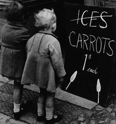Due bambine osservano l'insegna di un negozio che pubblicizza due carote anziché due ghiaccioli, 28 aprile 1941. In tempo di guerra simili sostituzioni erano necessarie vista la scarsità di cioccolato e altri dolci. (Fox Photos/Getty Images)