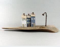 Drie beetje geschilderd, noodlijdende huizen, elk met een roestige spijker voor schoorstenen en een gebogen roestige spijker voor een lampost, voeg gewoon een mooie natuurlijke zee gewassen stuk drijfhout met roestige merken en een paar natuurlijke gaten en je hebt een charmante originele ornament die een beetje zal genade plank ergens. Handgemaakt door ons in North Norfolk de statistieken zijn 19.5 cm lang ongeveer 4.5 cm breed en het hoogste huis staat slechts 6 cm hoog.