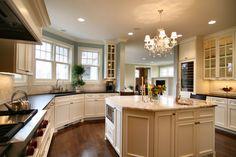 White kitchen with black quartz countertop. Kitchen with crystal chandelier over white kitchen island with marble countertop