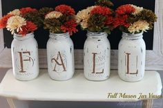 Pretty and easy-to-make fall mason jar vases. Repurposed mason jars are painted with white chalk paint and sanded slightly to give them a distressed look. Then stencils are used to create the word FALL, and the vases are filled with fall mums.