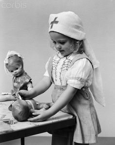 1940s child playing nurse with dolls