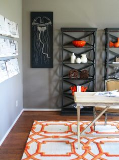 Chic gray & orange office design with gray walls paint color, rustic sawhorse desk, black X-back bookcases, Coral Arabesque Rug and Ballard Designs Languishing Drifters Giclee Print.
