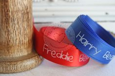 Personalised ribbon with names, using white foil on red and royal blue satin