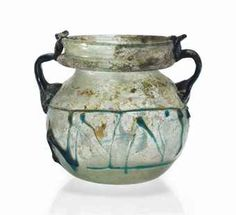 A ROMAN PALE GREEN GLASS JAR - CIRCA 4TH CENTURY A.D. - Free-blown, with a spherical body, a short neck and a wide collared rim, with blue applied zigzag trails on the body and two handles attached to the shoulders and pulled up to the rim 3 ½ in. (9 cm.) high