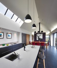 Art in the kitchen and dark floors and lower cabinets with white counters, white walls and no uppers - Isle of Skye House