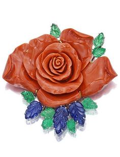 A coral, sapphire and emerald brooch, Sabbadini centering a carved coral rose, enhanced by carved sapphire and emerald leaves; signed Sabbadini; with box; mounted in eighteen karat white and yellow gold; length: 2 1/2in