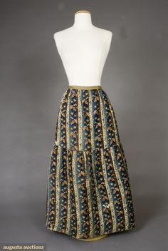 Printed wool petticoat, twill challis printed with stripes of blue, brown and cream, overlaid with red oak leaves and roses, deep flounce on lower half, hand quilted in vertical and diagonal bands to brown linen lining with cotton batting, linen waistband, chocolate brown velvet hem binding, French, 1835-1855