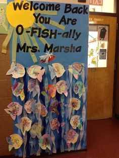 Welcome back poster for a teacher returning from getting married. Blue paper, streamers for water, yellow cardstock for sun, letters from Staples. Have each student decorate a fish. Welcome back to SCHOOL you are now o-FISH-ally Mrs. -----