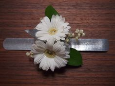 Always a favorite - white gerber corsage, encrusted with rhinestone centers, lily of the valley and ribbons on a silver cuff.  www.urbanelementsinteriorspace.com Portland, OR