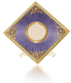 A Fabergé two-colour gold and enamel frame, workmaster Michael Perchin, St Petersburg, 1895-1899 square resting on one corner, the ground of translucent lavender enamel over sunburst engine-turning within a laurel border, the corners applied with tied ribbons each set with a seed pearl, the circular aperture within a beaded bezel, later faux ivory back, gold strut.