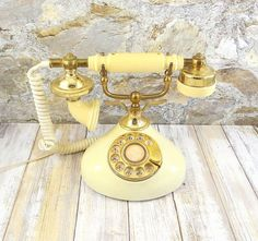 Wonderful working vintage 70s reproduction of the 1920s French Style telephone. Features ivory color on the base and handle with brass. finish base and cradle, heavy plastic receiver. Original cords. In amazing vintage condition. It measures 6.5 X 5.5 at the base and stands 7 tall and features an ivory colored plastic body with gold plastic accents gold-tone metal receiver stand. It has an 8 long wire that is hard-wired into base and plugs into a modern modular jack. There is a light cameo…
