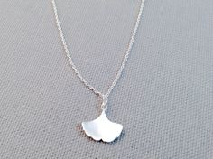 Silver Ginkgo Necklace. A simple Ginkgo leaf dangles sweetly from this silver chain necklace. This lovely sterling silver necklace is 16 inches long with a 2 inch extension with pale green bead charm on the end and lobster clasp closure.