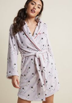 Relaxing Atmosphere Robe - Slip into this quirky bathrobe, close your eyes, and imagine yourself gliding through the skies. It's not that hard seeing as this cozy layer's soft fleece feels like floating on a cloud! Printed with astronauts chillin' on a lilac-grey backdrop, satiny burgundy piping, and inner ribbon ties, this sash-topped robe is ideal for stylish spacing out.