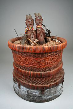 Divination Basket (Kitumba-Ngombo)     19th–20th century    Democratic Republic of the Congo,  Culture: Holo peoples   Rattan, mud, wood, beads, metals, feathers