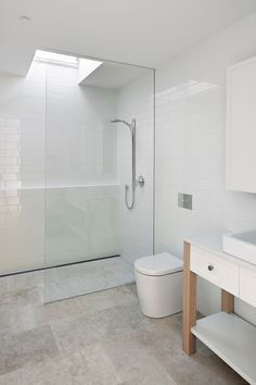 All-white bathroom with glass shower area and skylight