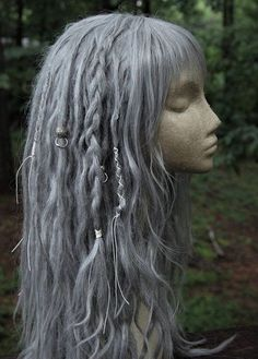 READY TO SHIP!! One of a kind, will not be replicated! This is a standard cap fair silver dreadlock wig with short, choppy, asymmetrical bangs and an assortment of decor including pure white wraps, silver beads, silver hair rings and thick braids. 27 in long layers layered, very full and natural Bangs can be adjusted in length with placement of cap Message me for any and all questions or comments! *****