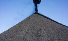 Coal falls from an elevator onto a storage pile