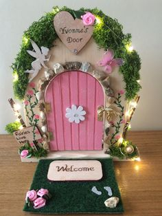 This beautiful door has been made with care and attention to detail. Personalised on a wooden heart at the top and hand painted using acrylics and a touch of magic sparkle. Each door will have willow to hang the lights, a fairy shape and a lovely little sign with the words Fairies