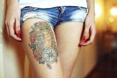 Owl and roses on leg - Charming tattoo in the form of an owl created in traditional American style. Recently owls gained enormous popularity among girls, and it is the front of the thigh that became a favorite place for the application of this tattoo. Often owl tattoos complement by image of a compass, clock or colorful flowers.