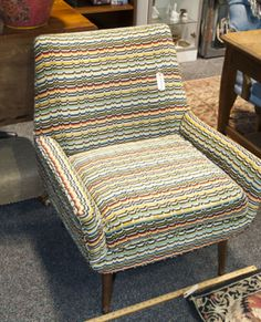 FUNKY CONTEMPORARY CASCADIA ARMCHAIR FROM THE FREESTYLE COLLECTION BY SIGNATURE FURNITURE FOR ASHLEY. THIS MID CENTURY STYLE CHAIR IS IN EXCELLENT CONDITION. IT HAS A MULTI COLOR HEART BEAT BANDED PATTERN WITH TAPERED WOOD LEGS. ADD COLOR TO ANY ROOM WITH THIS BEAUTY.
