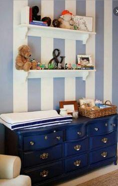 Cômoda para quarto de bebê azul marinho e parede listrada.