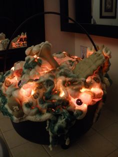Todays project finished: glowing cauldron of 'parts'. Lg plastic cauldron. Make hole in bottom for lights. Fill w/newspaper or plastic bags. Position lights above paper/plastic. Cover w/1 layer of great stuff. Add 'parts'. Let dry. Spray paint here & there for effect. Cheap, fast & easy!