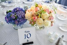 table number and blue and white flowers on white table cloth - table setting - preppy New York Sagamore resort wedding photo by New York wedding photographer Tracey Buyce