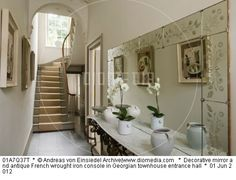 Decorative mirror and antique French wrought iron console in Georgian townhouse entrance hall