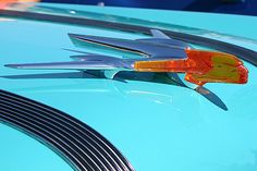 Once holding a place of honor as brand-defining symbols, awesome hood ornaments are now edging towards extinction. We've selected ten awesome ornaments which we're looking for you to name and answer the bonus obscure automotive history we've found on each.