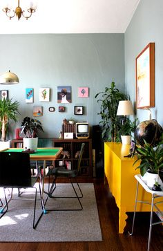 Love the bright yellow piece, wood, brass, and greyish blue. Plants always help, and big framed art!