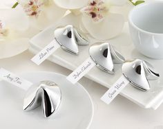 Fortune Cookie Place Card Holders: Good Fortune - A wonderful addition to your wedding, this silver-tone replica of a classic cookie will surely bring good fortune to your guests. Features and facts: Silver-tone fortune cookie with side slot to hold slender card, which can hold name or hand-written message Made of resin Sold as a set of four
