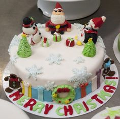 Christmas on a cake, icing Santa, Gingerbread men, snowman, penguin, presents, reef, presents and trees.