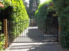Single swing gate with posts wrapped in brick masonry for Single wooden driveway gates
