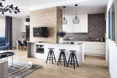 Kuchnia ma nowoczesny, geometryczny rys. Szara tapeta ładnie komponuje się z białą wyspą kuchenną, kubistycznymi lampami i czarnymi hokerami. Szare blaty kuchenne błyszczą, a wyspa kuchenna urzeka wytłaczanym wzorem.