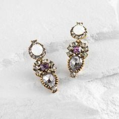 The vivacious design of these antiqued gold drop earrings showcases a glimmering array of glass stones in purple, gray, opaline and hematite hues.