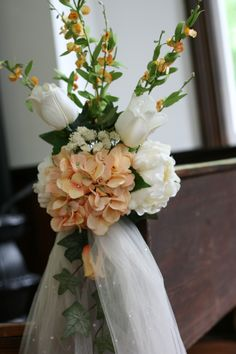 Church isle decorations using cream and orange silk flowers with ivory tuelle.