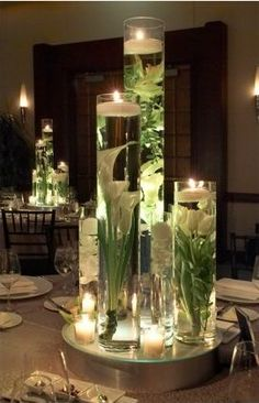 Tall Cylinder vases with different flowers inside and floating candle on top.