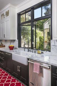 Farmhouse sink with traditional two-toned cabinetry creates an inviting kitchen space that is perfect for family or guests. The bold red Dhurrie rug gives this room some added character.