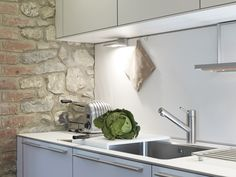Simple white kitchen units with bulthaup's stylish wing lights are beautifully offset against the traditional stone wall. Kitchen Design | bulthaup Exeter | Sapphire Spaces - bulthaup b3 kitchen