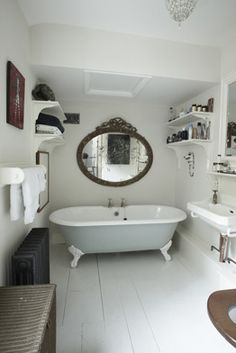 Claw foot bath, back wall in small, white round tiles. Add a rainfall shower head in the middle, pretty shower curtains and a valance - stunning focal piece for a small bathroom!