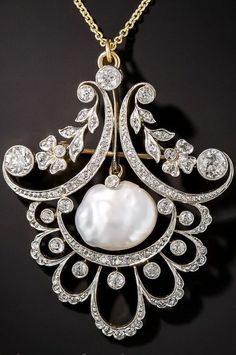 Edwardian Pearl and Diamond Pendant. Graceful garlands of diamond-set flowers, leaves, scallops and swirls frame a luminous baroque fresh water pearl displaying exceptional luster and orient in this exemplary example of Belle Époque design, hand fabricated in platinum over 18K yellow gold - circa 1900. This elegant fin de siècle jewel can be worn as either a pendant or a brooch. Measuring 1 3/4 inch by 1 7/16 inch. Exceptionally elegant.